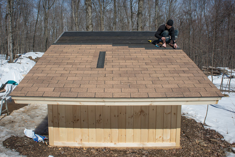 Tyler Affixing Shingles to Solar Shed Roof