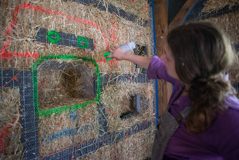 Tara Painting Face Around Nook in Strawbale Wall