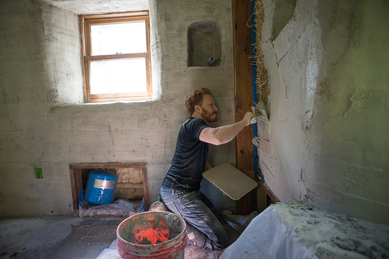 Tyler Plastering the Interior of Straw Bale Cottage