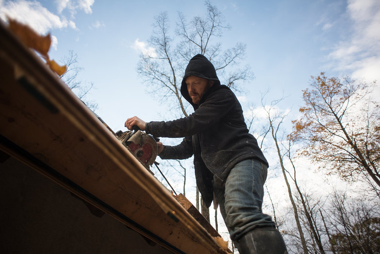 Tyler Cutting Excess Plywood on Cottage Roof
