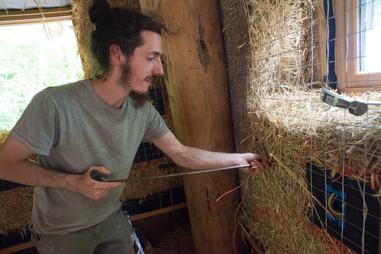 Owen Threading Baling Twine Through Wall