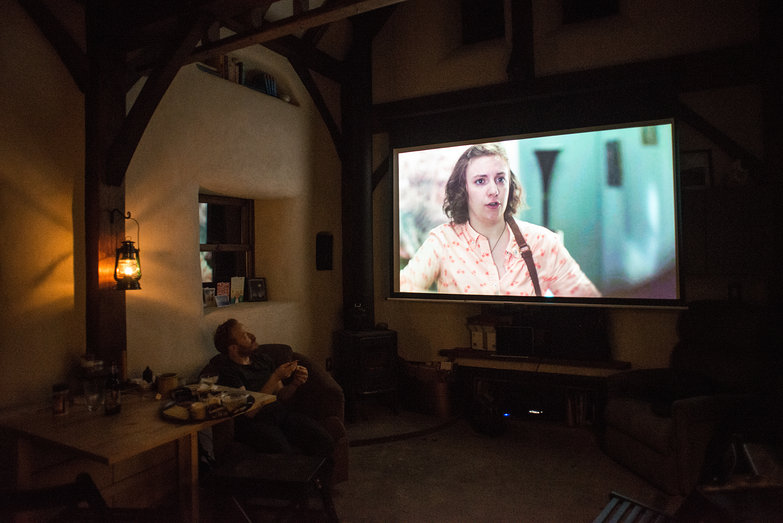 "Tiny Straw Bale Cottage Movie Theater: Tyler watching ""Girls"" on the Big Projector Screen"