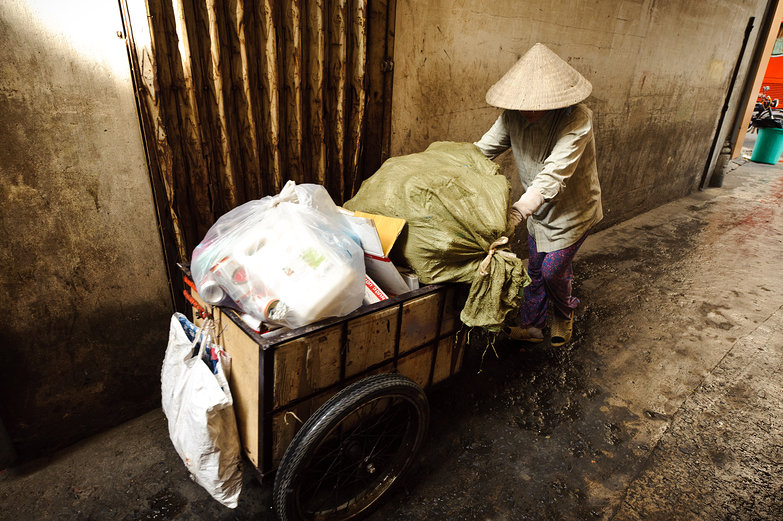 Woman Pushing Cart in Ho Chi Minh City Alleyway