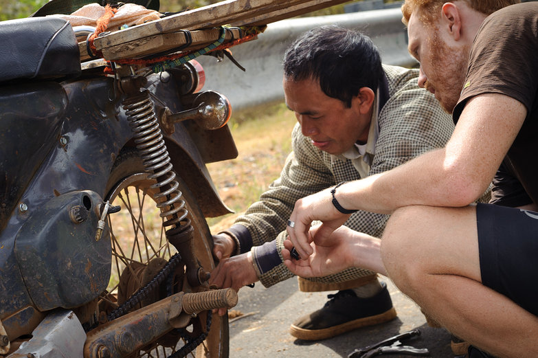 Tyler & Vietnamese Man Examining Flat Tire