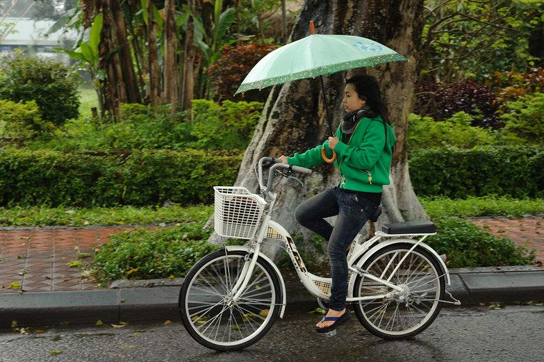 Huế Cyclist with Umbrella