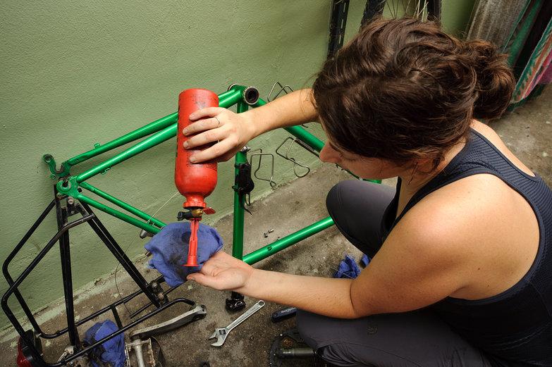 Tara Using Gas to Clean Tar off Bike