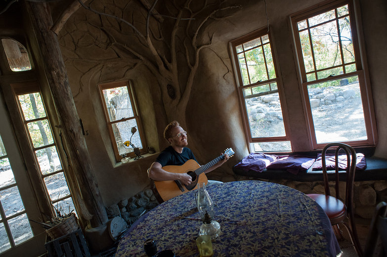 Tyler Playing Guitar in Strawbale Cottage