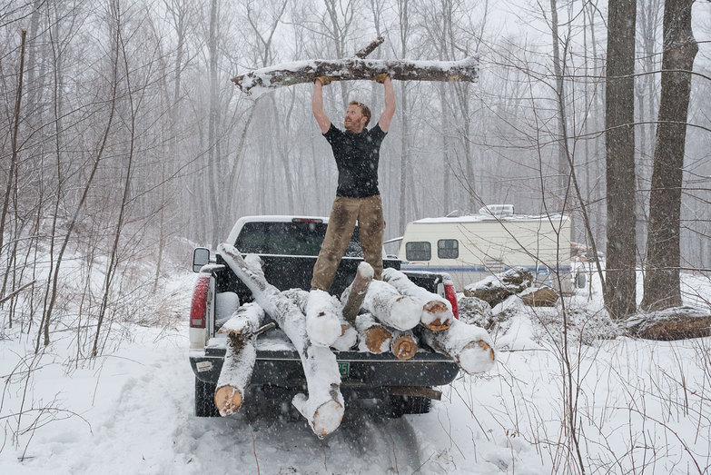 Tyler Lifting Log Triumphantly in our Truck (Collecting Knee Braces for Timber Frame)