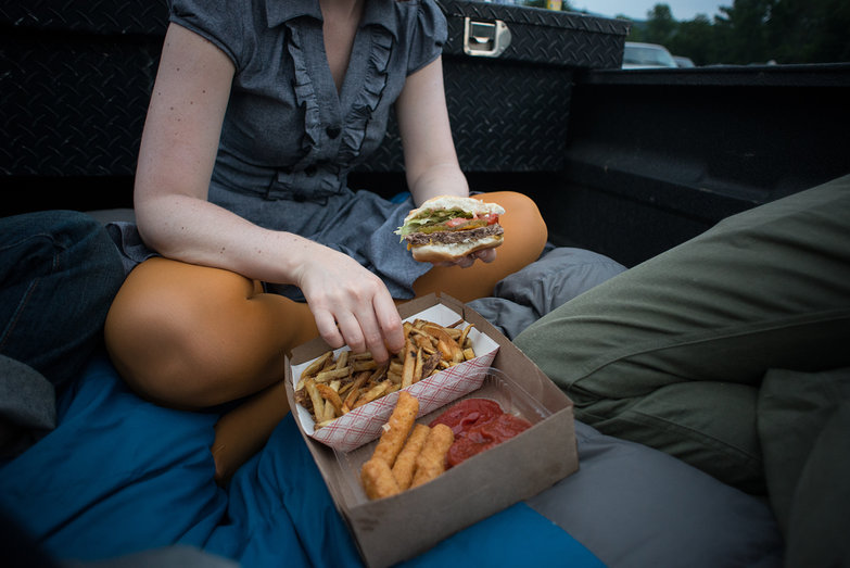 Katherine Eating Cheeseburger At Drive-In Movie Theater