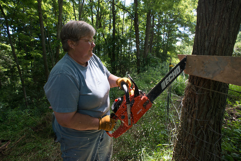 Kathy Chainsawing Pointy End off Wood